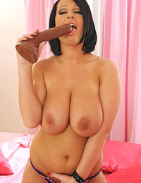 Busty LaTaya Roxx playing with a huge brown dildo on bed